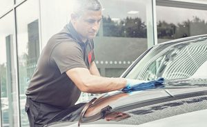 Big image of a man cleaning a car.